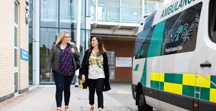 Two women outside a hospital near an ambulance