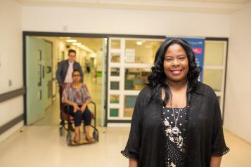 Woman in hospital smiling at the camera with a man pushing a woman in a wheelchair in the background