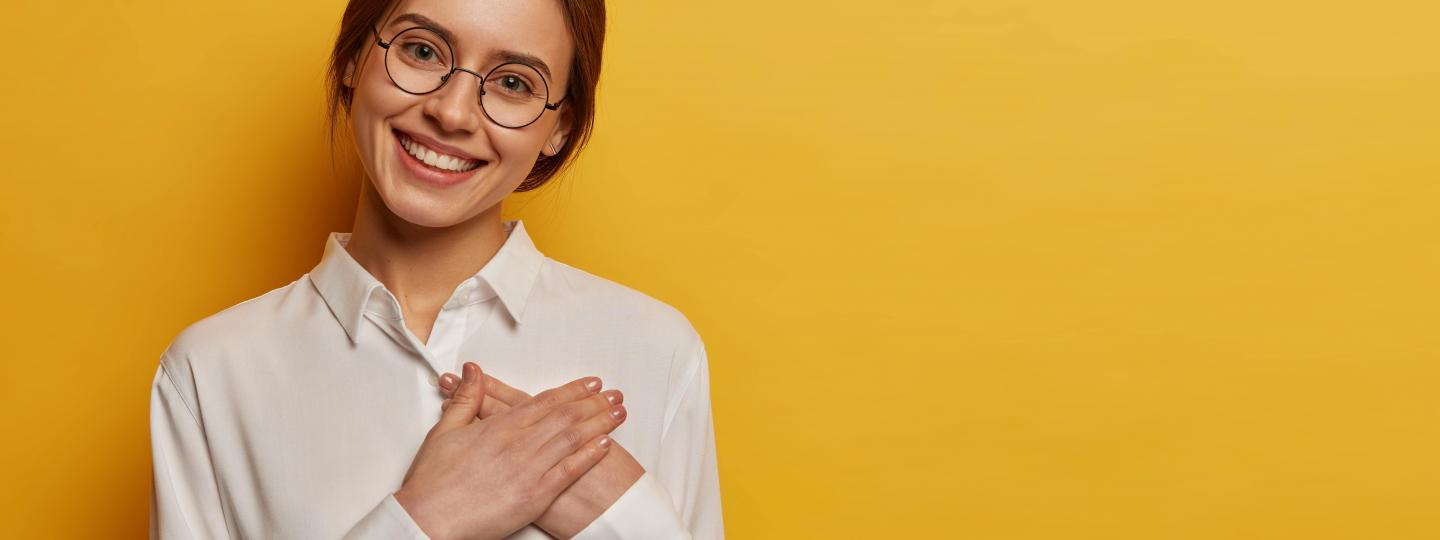 Charming positive woman presses hands to chest to gesture thank you