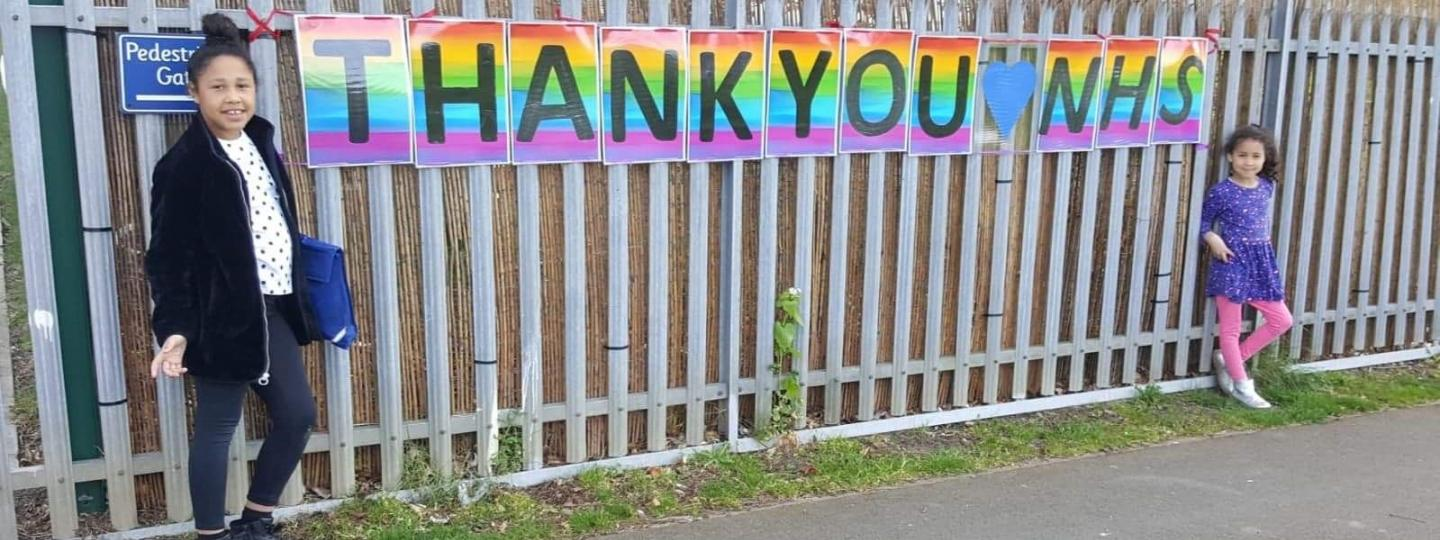 Two children standing next to fence with a thank you banner